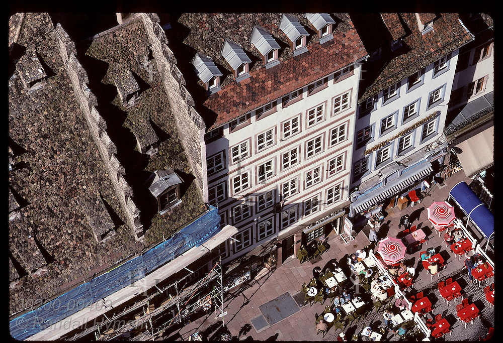 View atop the Cathedral of people and red cafe umbrellas on plaza in center of Strasbourg. France