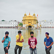 Men helping in retrieving water from Golden Temple's sacred pool.