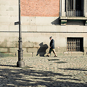 Photo taken in Central Madrid of a man in mid stride near the Plaza de Murillo.