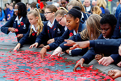 © Licensed to London News Pictures. 11/11/2015. London, UK. Students of Eltham Hil School throw remembrance poppies to the fountains in Trafalgar Square during Silence in the Square event as part of Armistice Day on Wednesday, 11 November 2015. Photo credit: Tolga Akmen/LNP
