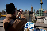 Tourist films Houses of Parliament on his camcorder at Westminster, London.