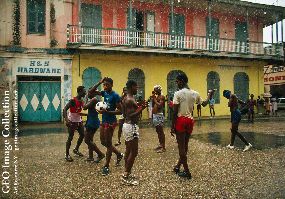 A group of teenagers play a game of soccer in the rainy streets of Cap Haitien.
