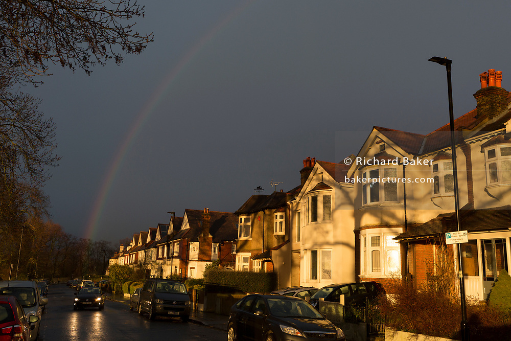 Dark skies and a brief rainbow arcing over south London residential Edwardian period homes after heavy rainfall, on 25th February 2020, in London, England.