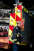 London. England UK. September 25th 2013. Shoreditch fire station. Firefighters strike from 12-4pm in a protest at threats to their pensions. A female firefighter stands in front of her engine.