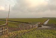 Buitendijks kweldergebied van waterschap Blija Buitendijks.<br /> Waterschap Blija Buitendijks is het kleinste waterschap van Nederland. Het waterschap beheert 100 hectare weiland, gelegen bij het dorp Blija in het noorden van Friesland, tussen de Waddenzeedijk en zomerdijk. Direct achter de 2,25 m +NAP hoge zomerdijk bevindt zich het uitgestrekte kweldergebied van de Waddenzee. Bij hoogwater (vloed) stroomt het buiten de zomerdijk gelegen kwelder regelmatig onder water. Bij extreem hoog water, bijvoorbeeld bij springtij en noordwesterstorm komt het zeewater vanuit de Waddenzee ook over de zomerdijk. De door het waterschap beheerde polder komt dan geheel onder water te staan, soms zelfs tot halverwege de Waddenzeedijk. Bij afgaand tij (eb) stroomt het zeewater via de klepstuwen in de zomerdijk terug naar de Waddenzee. <br /> De afgebeelde watergangen (afwateringssloten) bevinden zich op deze foto langs en loodrecht op de zomerdijk (op de voorgrond) met daarin de betonnen duikers met klepstuwen. Via de dammen in de watergang kunnen de veehouders vanaf hun weilanden op de zomerdijk en de daarachter gelegen kwelders komen. <br /> Op de achtergrond is in de verte de Waddenzeedijk (op Deltahoogte) te zien.