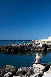 Pescatore con canna sugli scogli vicino a al porto di Gallipoli (LE)