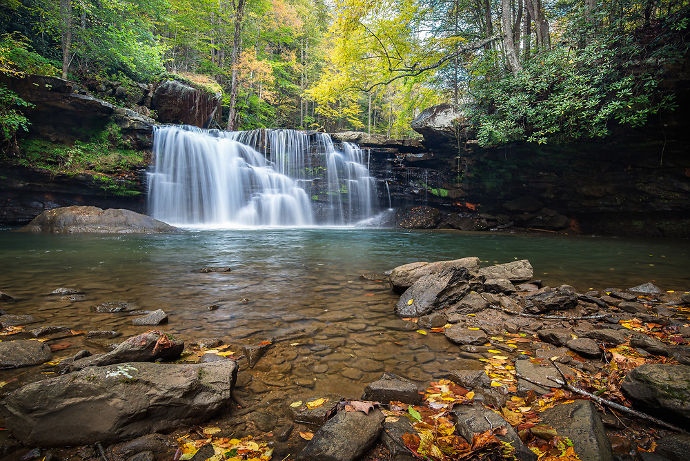 The falls of Mill Creek in Ansted, West Virginia fall delicately over the rocky ledge brushed with peak season autumn foliage above,  dotted with an array of warm colored leaves below.