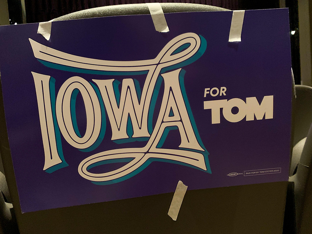 Iowa for Tom sign hangs on the back of an auditorium chair.