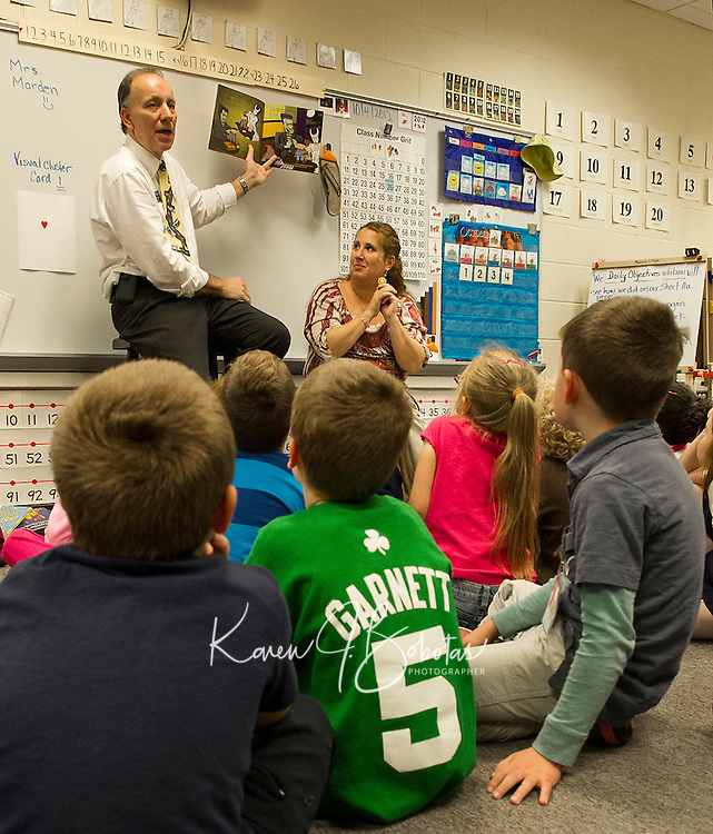 """Participating in the """"Read for the Record"""" early childhood literacy campaign LRCC President Dr. Scott Kalicki reads """"Frankie Stein"""" as Mrs. Chase uses sign language for the first grade students in Mrs. Faria's and Mrs. Olson's classrooms at Pleasant Street School Thursday afternoon.  (Karen Bobotas/for the Laconia Daily Sun)"""