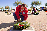 09 DECEMBER 2011 - PHOENIX, AZ:  KYLE GLUCK and ELIZABETH GLUCK lay a Christmas wreaths on a veterans' graves in Phoenix Saturday. Several hundred volunteers and veterans gathered at the National Memorial Cemetery of Arizona in Phoenix Saturday to lay Christmas wreaths on headstones, a tradition started by Wreaths Across America. Wreaths Across America is a nonprofit organization founded to continue and expand the annual wreath laying ceremony at Arlington National Cemetery begun by Maine businessman, Morrill Worcester, in 1992.   PHOTO BY JACK KURTZ