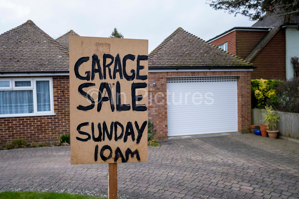 A sign reading 'Garage Sale Sunday 10am' appears in the front garden of a bungalow in front of the garage on the 14th of February 2020 on Bathurst road in Folkestone, United Kingdom.  A garage sale is a common informal sale of used goods by a private individual normally held in their garage and front garden.