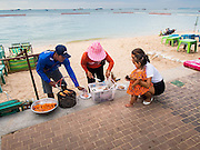 "26 SEPTEMBER 2014 - PATTAYA, CHONBURI, THAILAND: A vendor sells grilled prawns to a Thai woman and her child on Pattaya Beach. Pataya, a beach resort about two hours from Bangkok, has wrestled with a reputation of having a high crime rate and being a haven for sex tourism. After the coup in May, the military government cracked down on other Thai beach resorts, notably Phuket and Hua Hin, putting military officers in charge of law enforcement and cleaning up unlicensed businesses that encroached on beaches. Pattaya city officials have launched their own crackdown and clean up in order to prevent a military crackdown. City officials have vowed to remake Pattaya as a ""family friendly"" destination. City police and tourist police now patrol ""Walking Street,"" Pattaya's notorious red light district, and officials are cracking down on unlicensed businesses on the beach.     PHOTO BY JACK KURTZ"