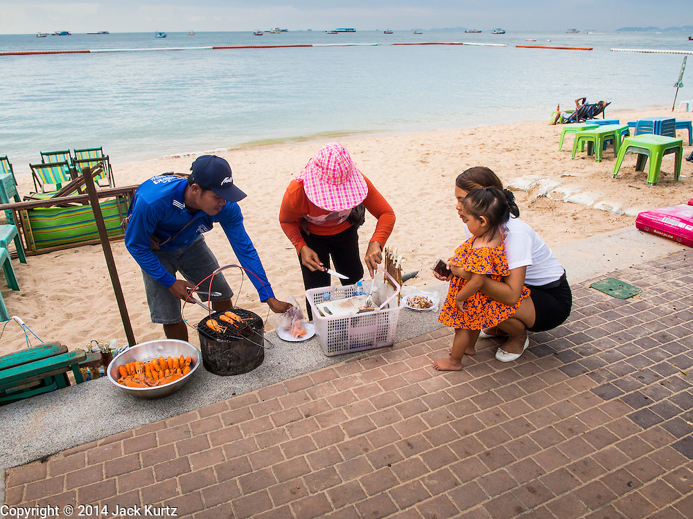 """26 SEPTEMBER 2014 - PATTAYA, CHONBURI, THAILAND: A vendor sells grilled prawns to a Thai woman and her child on Pattaya Beach. Pataya, a beach resort about two hours from Bangkok, has wrestled with a reputation of having a high crime rate and being a haven for sex tourism. After the coup in May, the military government cracked down on other Thai beach resorts, notably Phuket and Hua Hin, putting military officers in charge of law enforcement and cleaning up unlicensed businesses that encroached on beaches. Pattaya city officials have launched their own crackdown and clean up in order to prevent a military crackdown. City officials have vowed to remake Pattaya as a """"family friendly"""" destination. City police and tourist police now patrol """"Walking Street,"""" Pattaya's notorious red light district, and officials are cracking down on unlicensed businesses on the beach.     PHOTO BY JACK KURTZ"""