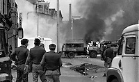 Burning barricade during the Lower Falls curfew. Soldiers look on. The British Army imposed during July 3 & 4, 1970, a 34 hour curfew (except for a two hour break to allow shopping) in approximately 50 streets in the Lower Falls district of Belfast, N Ireland, UK. A military helicopter hover overhead warning people they would be arrested if they remained on the streets. An army search during the curfew uncovered 100 firearms, 100 home-made bombs, 250 lbs of explosives, 21000 rounds of ammunition and 8 two-way radios. This curfew is often seen as a turning point in souring relations between the Roman Catholic working class and the British Army. Thereafter the army was no longer seen as the protector of the Catholic community. 197007030251R.<br />