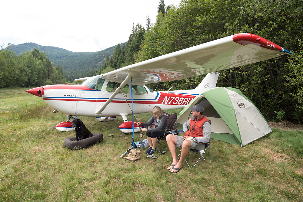 Couple camping by their airplane at the Minam River Lodge in Oregon's Wallowa Mountains.