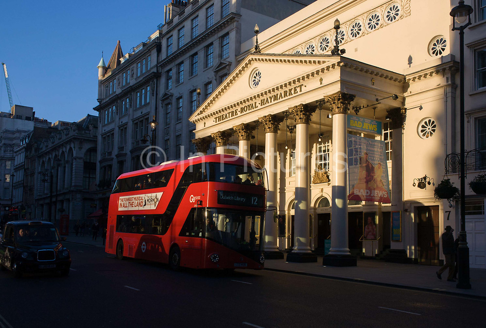 A number 12 Routemaster red London bus drives along on a late on a winter's afternoon, passing the sunlit exterior of the Haymarket Theatre in central London. Warm light shines on the pillars and columns of this famous cultural landmark in the borough of Westminster. The Theatre Royal, Haymarket (also known as Haymarket Theatre or the Little Theatre) is a West End theatre in the Haymarket in the City of Westminster which dates back to 1720, making it the third-oldest London playhouse still in use.