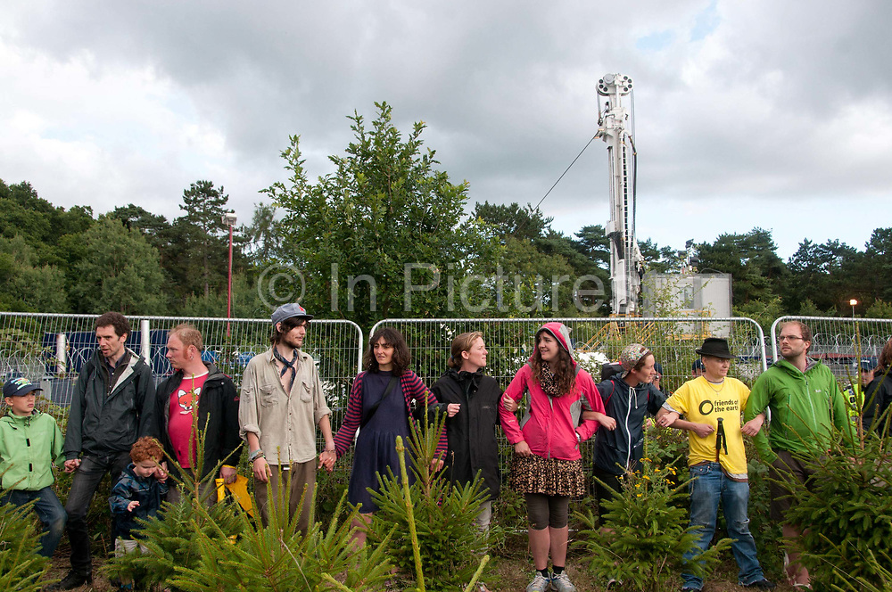 Balcombe, West Sussex. Site of Cuadrilla drilling. Demonstration against fracking 18.08.2013. Protesters surround the site and link arms.