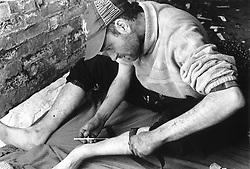 Man injecting drugs into his leg using syringe,