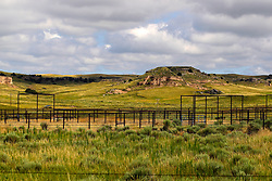 A steel fenced corral stands vacant but ready in front of of a bluff on the horizon in northwest Nebraska