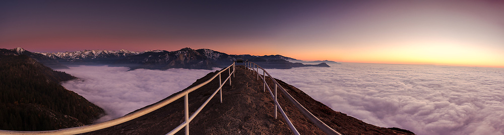 Panoramic view from Moro Rock of ocean of white clouds blanketing the Sierra Nevada Mountains at sunset with snowcapped peaks in the background