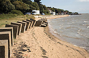 River Deben, Bawdsey quay, camper vans parked and second world war anti-landing concrete blocks in foreground to the river mouth, Bawdsey, Suffolk, England
