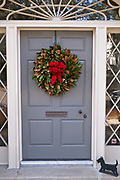 A historic home decorated with a Christmas wreath on Meeting Street in Charleston, SC.