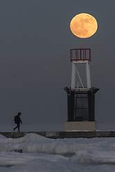 January 1, 2018 - Chicago, ILLINOIS, USA - CHICAGO, USA. A man walks across the jetty at the ice covered North Avenue beach as the supermoon rises on one of the coldest New Year's Days in decades.  The moon is at its closest point, the perigee, to Earth during its monthly orbit and appears 30% brighter and 14% larger.  January 2018 sees a supermoon known as a 'wolf moon' on 1 January and a 'blue moon' on 31 January. (Credit Image: © Stephen Chung/London News Pictures via ZUMA Wire)