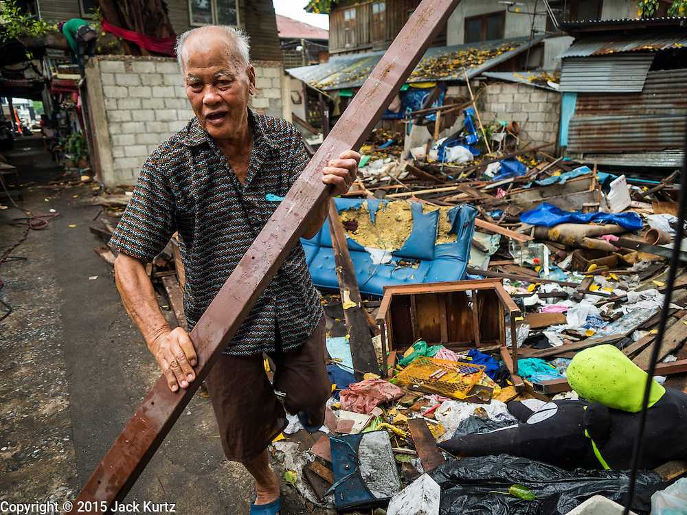 28 SEPTEMBER 2015 - BANGKOK, THAILAND: A man who lives near Wat Kalayanamit scavenges construction material from a home torn down by demolition workers. Fifty-four homes around Wat Kalayanamit, a historic Buddhist temple on the Chao Phraya River in the Thonburi section of Bangkok, are being razed and the residents evicted to make way for new development at the temple. The abbot of the temple said he was evicting the residents, who have lived on the temple grounds for generations, because their homes are unsafe and because he wants to improve the temple grounds. The evictions are a part of a Bangkok trend, especially along the Chao Phraya River and BTS light rail lines. Low income people are being evicted from their long time homes to make way for urban renewal.    PHOTO BY JACK KURTZ
