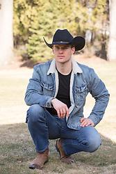 handsome cowboy in denim kneeling