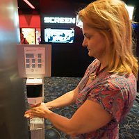 Guest sanitises her hands at a dispenser at the Cinema City movie theatre reopening during the ease of the COVID-19 restrictions in Budapest, Hungary on July 2, 2020. ATTILA VOLGYI