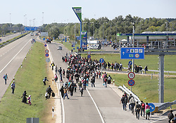 © London News Pictures. Migrants run from the police close to the Hungarian and Serbian border town of Roszke, Hungary, September 8 2015. The UN's humanitarian agencies are on the verge of bankruptcy and unable to meet the basic needs of millions of people because of the size of the refugee crisis in the Middle East, Africa and Europe, senior figures within the UN have told the media.   Picture by Paul Hackett /LNP