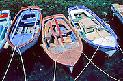 Three oar boats moor in emerald water at Thirasia Island (or Therasia), Greece.