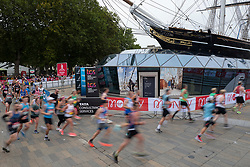 © Licensed to London News Pictures. 03/10/2021. London, UK. Runners pass the Cutty Sark as they take part in the 2021 London Marathon.This London Marathon will be the first full scale staging of the race in more than two years due to the Coronavirus Pandemic.  Photo credit: George Cracknell Wright/LNP