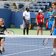 Andy Murray playing tennis with Jenna Cozier, 9, from Howard Beach, Queens. Reigning US Open champions Andy Murray and Serena Williams took part in the Tennis clinic with local Queens kids affected by Hurricane Sandy. Flushing. New York, USA. 22nd August 2013. Photo Tim Clayton