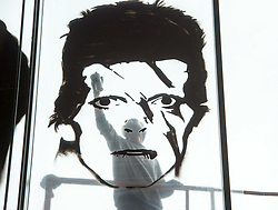 © Licensed to London News Pictures.  18/09/2017; Bristol, UK. VOYDER paints an image of David Bowie onto the front window of the Colston Hall. Colston Hall, Bristol's largest music venue, is to unveil a new mural painted in partnership with Upfest by Bristol artist Voyder of eight musical legends, each of which have performed at Colston Hall over the last 150 years, to celebrate the Colston Hall's 150th anniversary this week on 20 September.   The giant mural on the glass panes above the main entrance will feature portraits of Ella Fitzgerald, Louis Armstrong, David Bowie, Debbie Harry (Blondie), Jimi Hendrix, Mick Jagger, Sergei Rachmaninoff and Paul McCartney. The mural will be in place in time for Colston Hall to mark its anniversary with a big free Birthday Bash on Wednesday 20 September, exactly 150 years from when the venue first opened, to which all of Bristol is invited. Highlights for the night will include the world-famous Ukulele Orchestra of Great Britain, immersive projections from Limbic Cinema and toe tapping swing music from the Bruce/Ilett Big Band. The free event will begin at 6.30pm and see a complete takeover of the building, giving people the chance to explore every corner, stumbling across musicians, DJs, installations and projections, as acts pop up to create a unique party atmosphere. Colston Hall first opened its doors to the public on the 20th September 1867, after The Colston Hall Company bought the land from Colston Boy's School in 1861 to fulfil their vision of building a concert hall in the city. The Hall has seen four iterations in its 60 years, with the fourth and present Colston Hall opening in 1951. Picture credit : Simon Chapman/LNP
