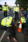 12 local activists locked themselves in specially made arm tubes to block the entrance to Quadrillas drill site in New Preston Road, July 03 2017, Lancashire, United Kingdom. Medics attending an activist hurt by police. The 13 activists included 3 councillors; Julie Brickles, Miranda Cox and Gina Dowding and Nick Danby, Martin Porter, Jeanette Porter,  Michelle Martin, Louise Robinson,<br /> Alana McCullough, Nick Sheldrick, Cath Robinson, Barbara Cookson, Dan Huxley-Blyth. The blockade is a repsonse to the emmidiate drilling for shale gas, fracking, by the fracking company Quadrilla. Lancashire voted against permitting fracking but was over ruled by the conservative central Government. All the activists have been active in the struggle against fracking for years but this is their first direct action of peacefull protesting. Fracking is a highly contested way of extracting gas, it is risky to extract and damaging to the environment and is banned in parts of Europe . Lancashire has in the past experienced earth quakes blamed on fracking.