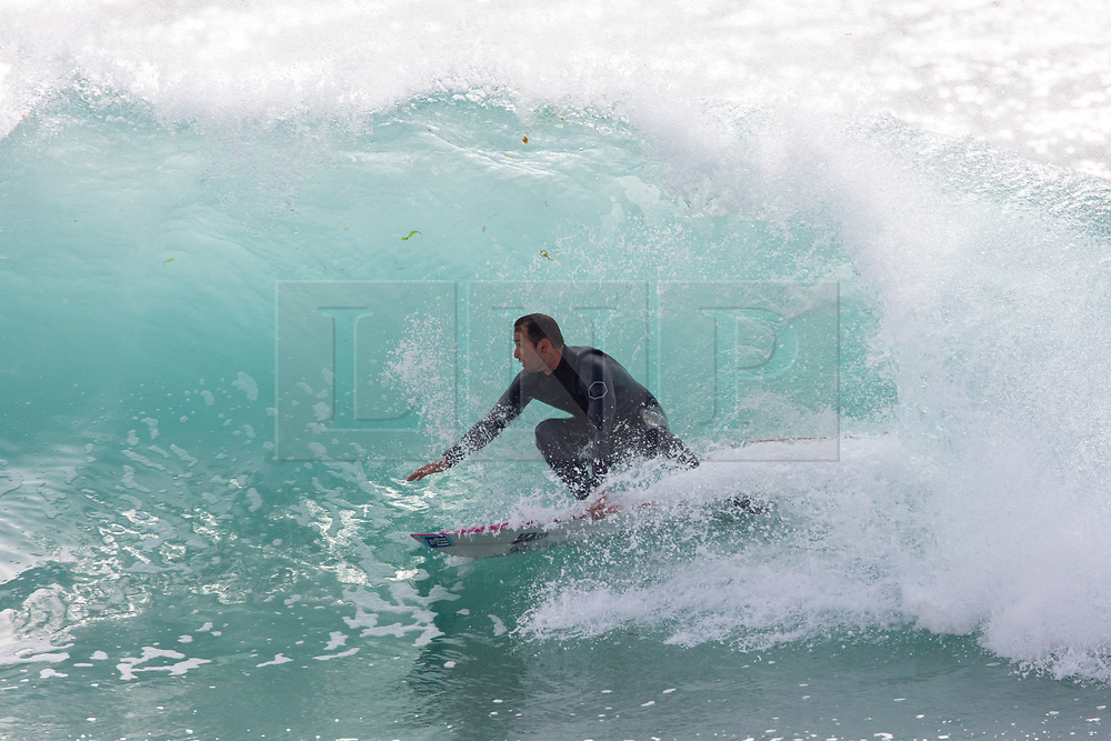 © Licensed to London News Pictures. 21/05/2020. Padstow, UK. A surfer catches a wave near Padstow on the north coast of Cornwall during a spell of hot weather. There is currently no RNLI Lifeguard service in the county due to Coronavirus (Covid-19), potentially causing issues across the upcoming bank holiday weekend as a large swell is due to hit Cornwall. Photo credit : Tom Nicholson/LNP