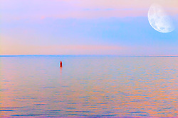 An isolated boey off the shore of Lake Superior in Minnesota stands in solitude under the morning sunrise under bright moon still visible.