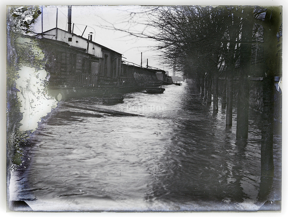 eroding glass plate with image of houseboats on river during flood, flooding Seine River Paris January 1910