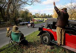 Participants in the Bonhams London to Brighton Veteran Car Run pass spectators in Staplefield, Sussex.