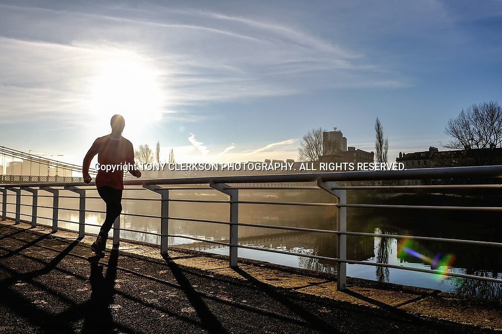 A jogger braves the cold along the River Clyde as Glasgow emerges from morning fog