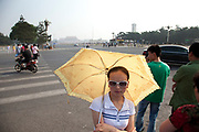 Tourist with an umbrella on Tiananmen Square protects herself from the sun. Beijing, China.