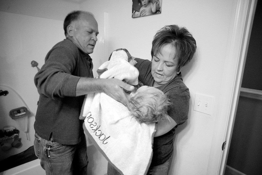 """Grandfather Frank lifts Kade from a bath into Fawn's arms being careful to support his neck. His four grandparents trade off caring for him during the day. """"If we didn't have both sets of grandparents to help, one of us would have had to quit our job,"""" says Kade's father Josh."""