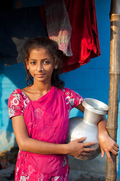 Rani Basfur, age 13 with a pot of water outside her house.<br /> <br /> Rani lives in Horijon Polli, a slum in which all residents are from the low-caste Hindu sweeper community. The community are ostracised from wider society and there are very few employment opportunities for them beyond cleaning. Oxfam are building a latrine block in Horijon Polli and are working with partners NGO Forum to support residents.<br /> <br /> Photo: Tom Pietrasik<br /> Mymensingh, Bangladesh<br /> November 17th 2014