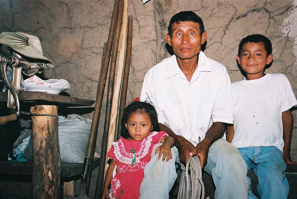 A Maya Chortí man and his children at home in the Copán region of Honduras