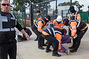 Security guards working on behalf of HS2 forcibly remove an environmental activist from HS2 Rebellion from the road in front of a gate providing access to a site for the HS2 high-speed rail link on 12 September 2020 in Harefield, United Kingdom. Anti-HS2 activists continue to try to prevent or delay works on the controversial £106bn HS2 high-speed rail link in the Colne Valley where thousands of trees have already been felled.