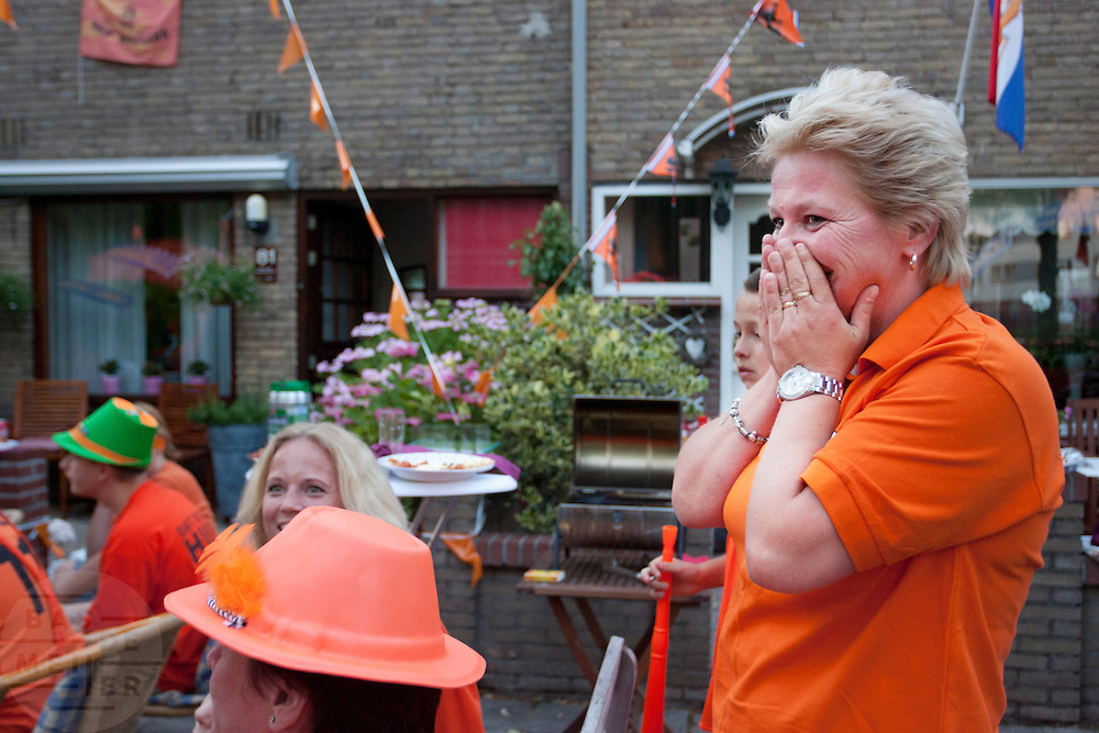 Bianca Lodder (rechts) kijkt gespannen naar de finale van het WK op een televisie buiten in de Utrechtse volkswijk Ondiep. Lodder is een lerares die Wesley Sneijder, die uit Ondiep komt, in de klas heeft gehad.<br /> <br /> Supporters are watching the World Championship Soccer 2010 on the street in the Utrecht district Ondiep. Amongst them is Bianca Lodder (right), former teacher of the Dutch player Wesley Sneijder.