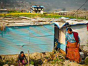 01 MARCH 2017 - KHOKANA, NEPAL: Woman chat in front of the temporary shelters they live in. Their homes were destroyed in the 2015 earthquake. Recovery seems to have barely begun nearly two years after the earthquake of 25 April 2015 that devastated Nepal. In some villages in the Kathmandu valley workers are working by hand to remove ruble and dig out destroyed buildings. About 9,000 people were killed and another 22,000 injured by the earthquake. The epicenter of the earthquake was east of the Gorka district.     PHOTO BY JACK KURTZ