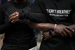 """Cryserica Jeter and Ray Smith-Byrd, of Detroit, link arms as they listen to """"Amazing Grace"""" outside the memorial service for George Floyd at North Central University in Minneapolis on Thursday, June 4, 2020. (Aaron Lavinsky/Minneapolis Star Tribune/TNS)"""
