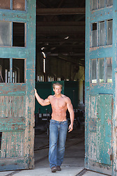 shirtless muscular man standing by large wooden doors